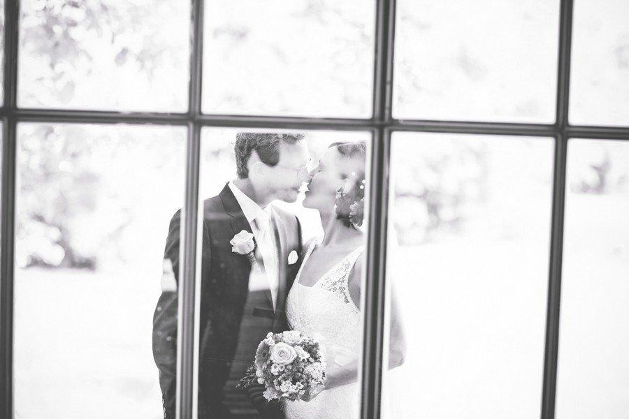Kuss von Braut und Bräutigam hinter einem Fenster auf dem Irghof. Foto: Stefanie Danner.