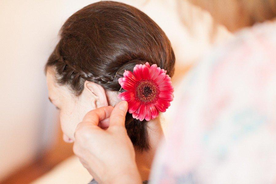 Hochzeitsfrisur mit einer echten Blume, einer roten Gerbera.