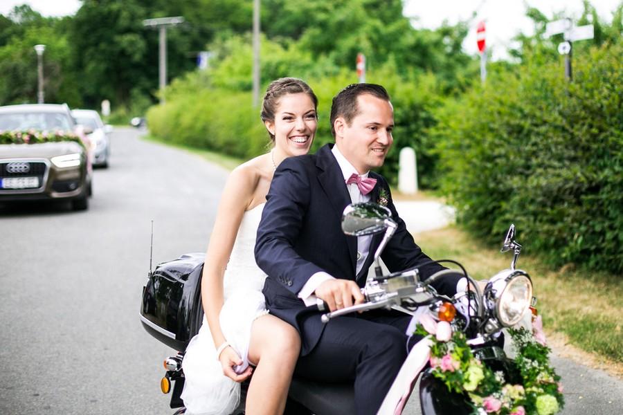 Braut und Bräutigam auf einem Moped.