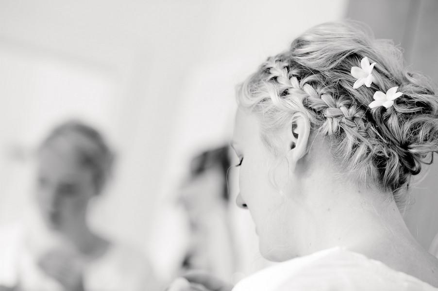 Brautfrisur für langes Haar mit seitlich geflochtenem Zopf und natürlichem Lockendutt.