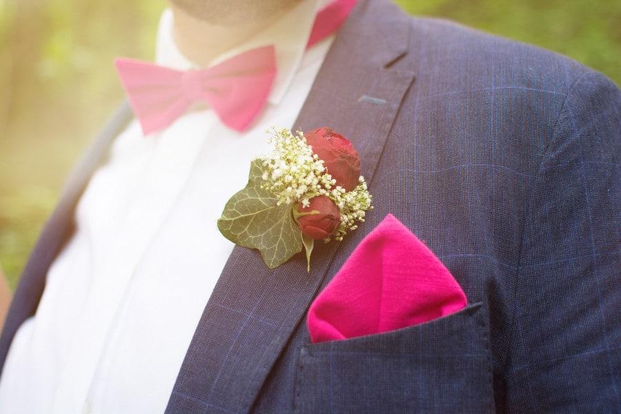 Modischer Bräutigam mit pinker Fliege und pinkem Einstecktuch