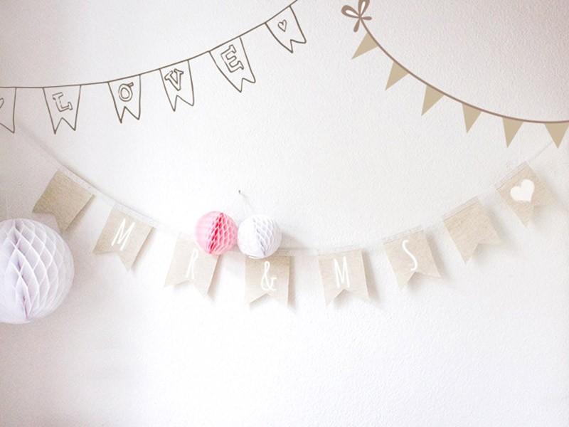 Selbstgemachte Wimpelkette aus Leinen als Deko für eine Hochzeit.