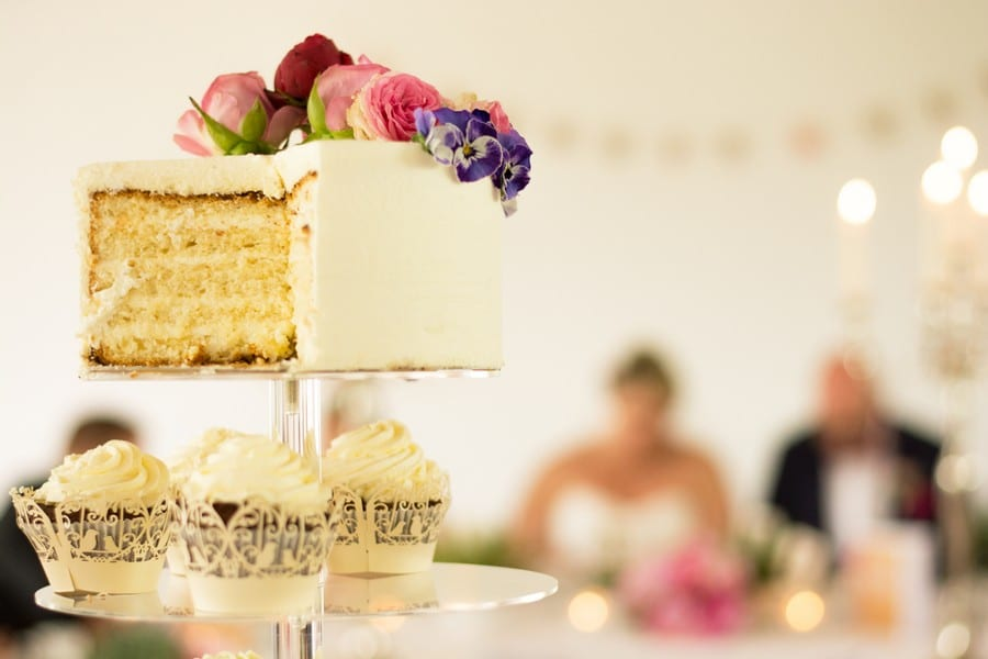 Hochzeitstorte aus Buttercreme mit echten Blumen in rosa und lila.