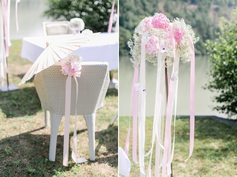 Rosa-weiße Blumendeko mit Bändern bei einer Trauung unter freiem Himmel