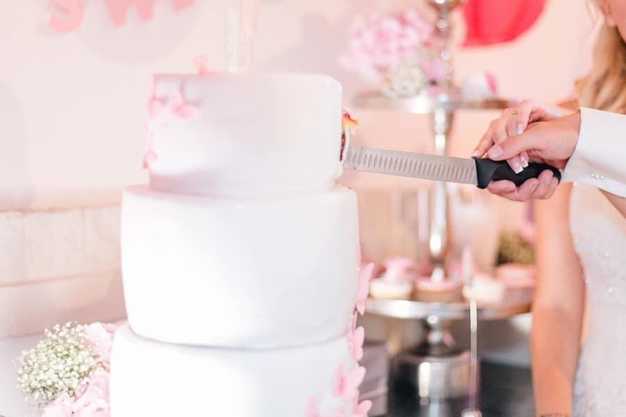 Eine Hochzeitstorte in Weiß und Rosa mit Blütenblättern