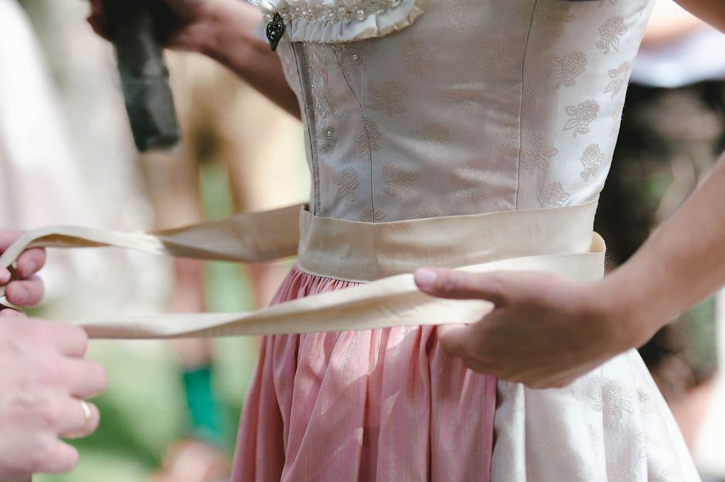 Traditionelles Umbinden der Schleife von links nach rechts nach der Hochzeit
