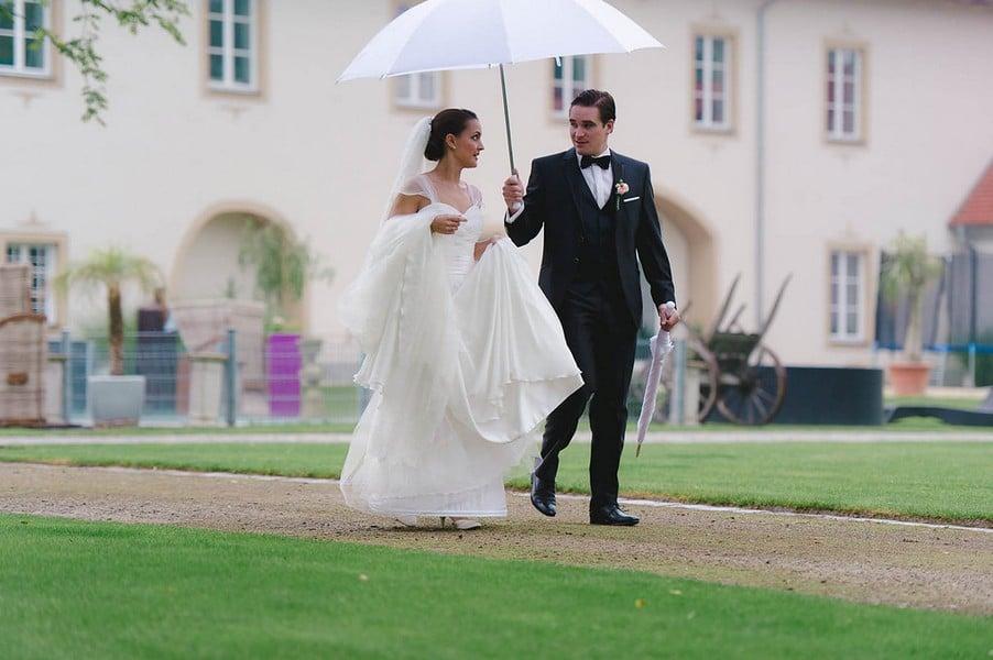 Hochzeitsfotos im Regen mit Braut unter dem Regenschirm