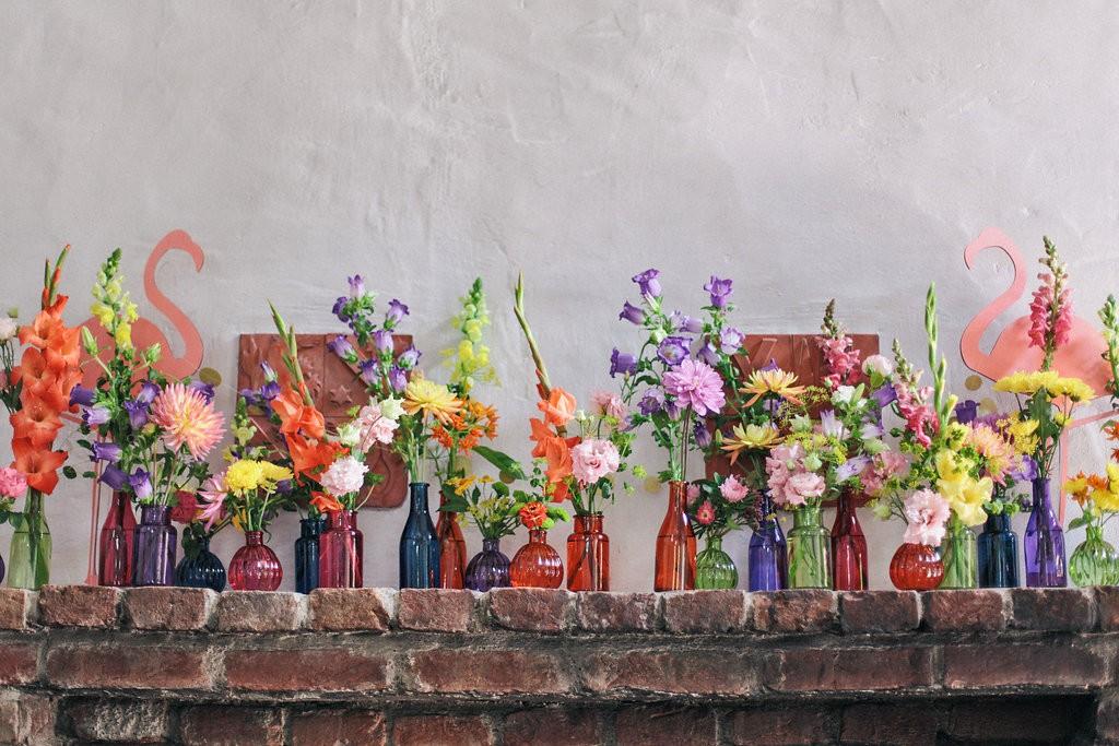 Bunte Gläser, Vasen und Blumen als Deko bei einer Sommerhochzeit