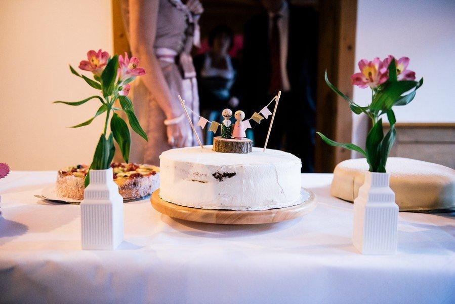 Kleine Hochzeitstorte in weiß mit individuellen Holzfiguren als Topping