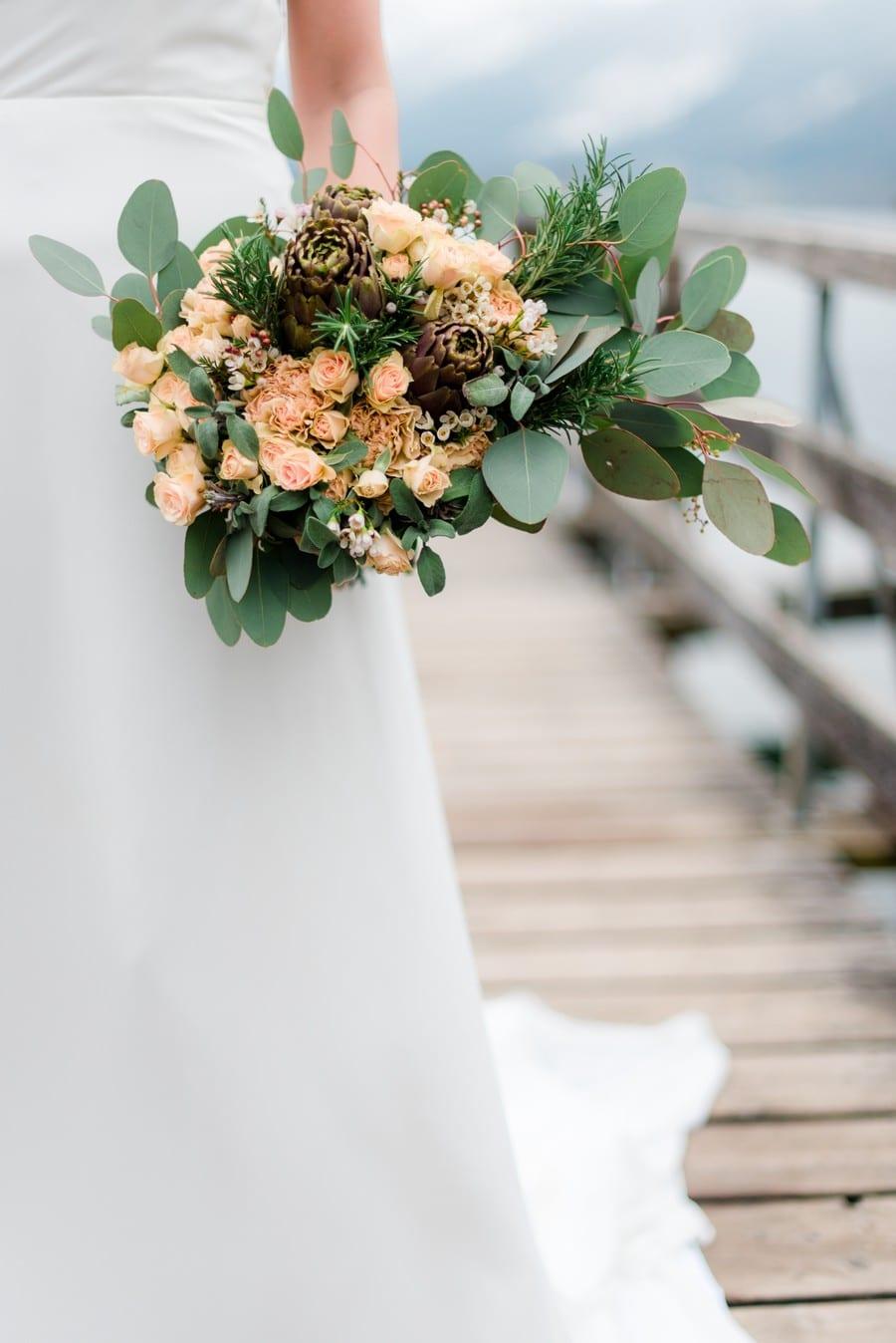 Ein natürlich-winterlicher Brautstrauß in Blassrosa, Peach und Grün, mit Artischocken und Eukalyptus-Blättern