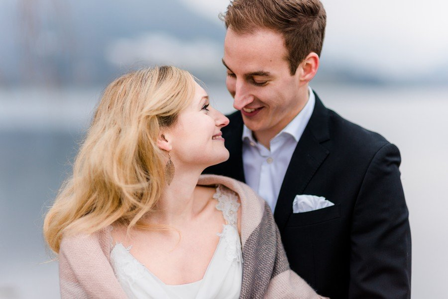 Ein Brautpaar-Shooting mit Boho-Vintage-Brautkleid mit Schleppe und Spitze auf dem Steg am Schliersee