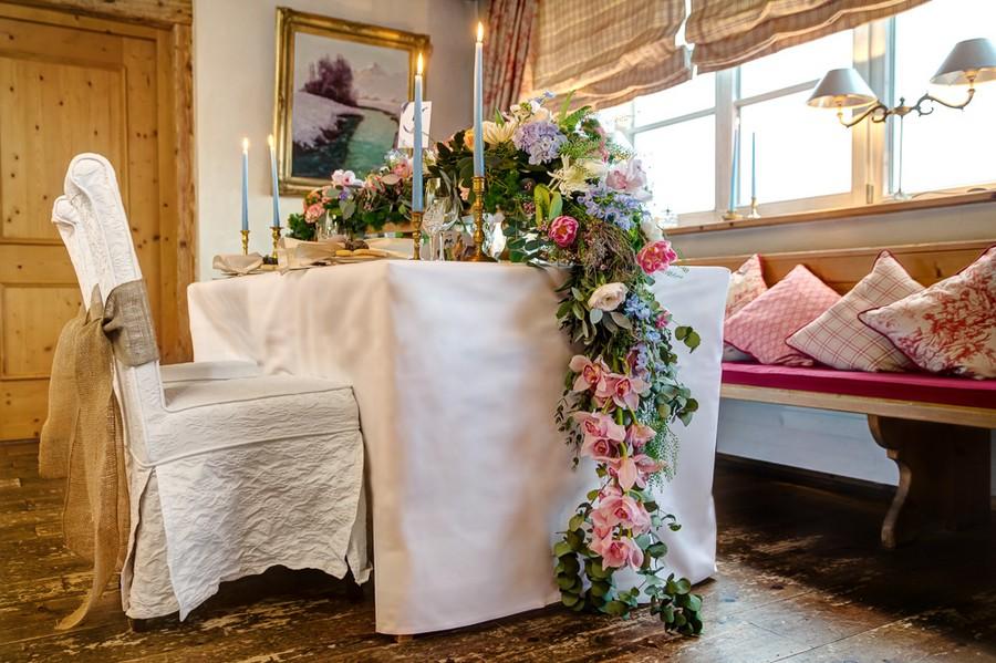 Üppiger Boho-Blumenschmuck für eine Hochzeitstafel