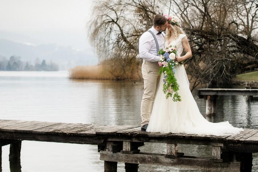 Boho-Braut und Bräutigam auf Steg mit herabwallendem Brautstrauß