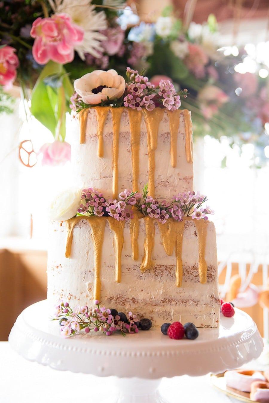 Ausgefallene Hochzeitstorte im naked cake Stil in weiß mit lila Schleierkraut und gelbem herablaufenden Zuckerguss