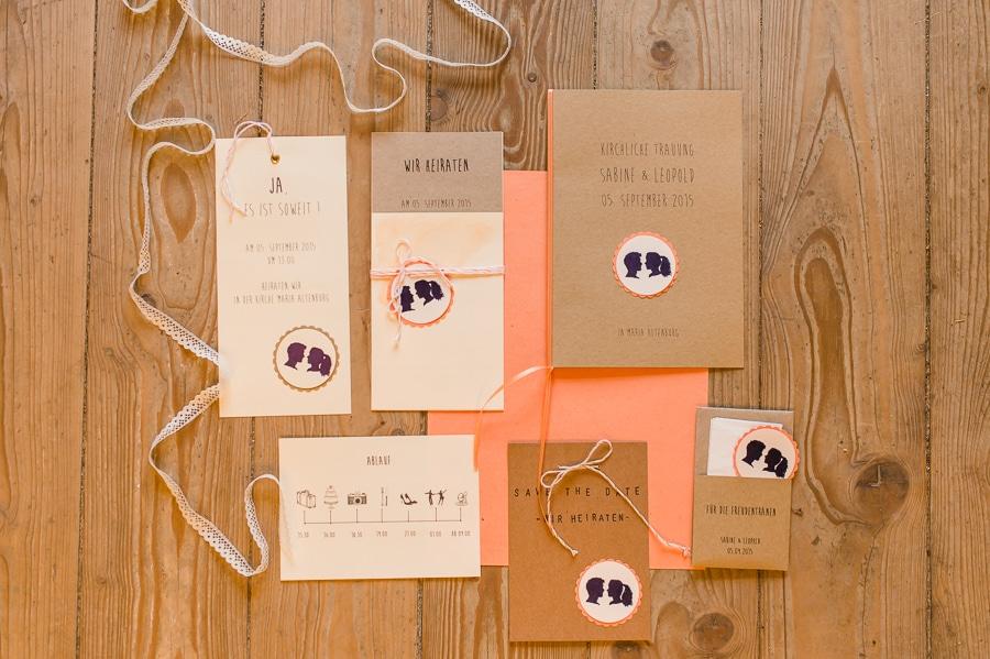 Papeterie für eine Hochzeit mit Kraftpapier und Scherenschnitt Emblem in braun und Pirsich