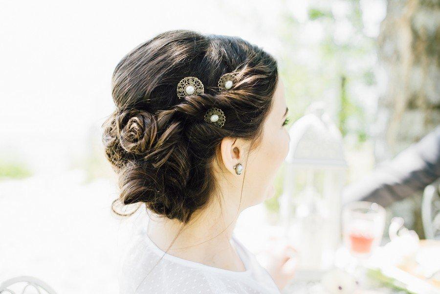 Brautfrisur zum Hochstecken im 20er Jahre Stil mit bronzefarbenen Haarnadeln und kleiner Perle