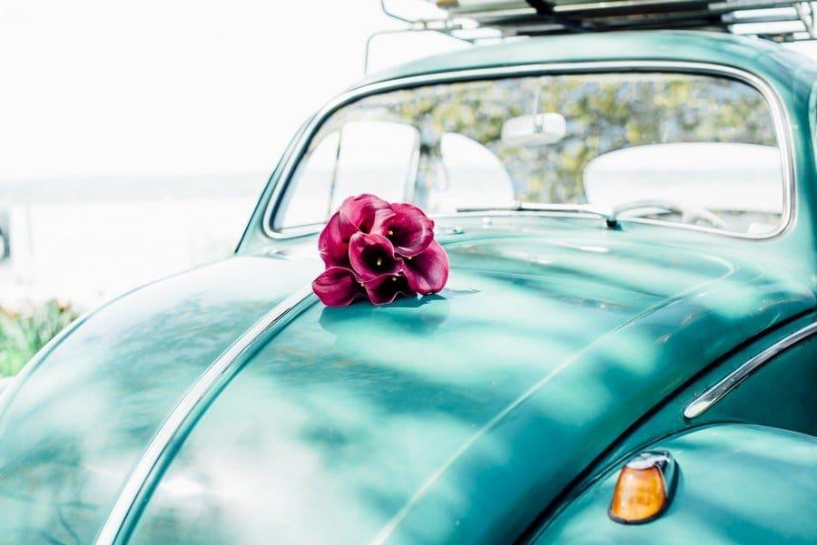 Schlichter Brautstrauß mit roten Calla auf einem Käfer als Brautauto