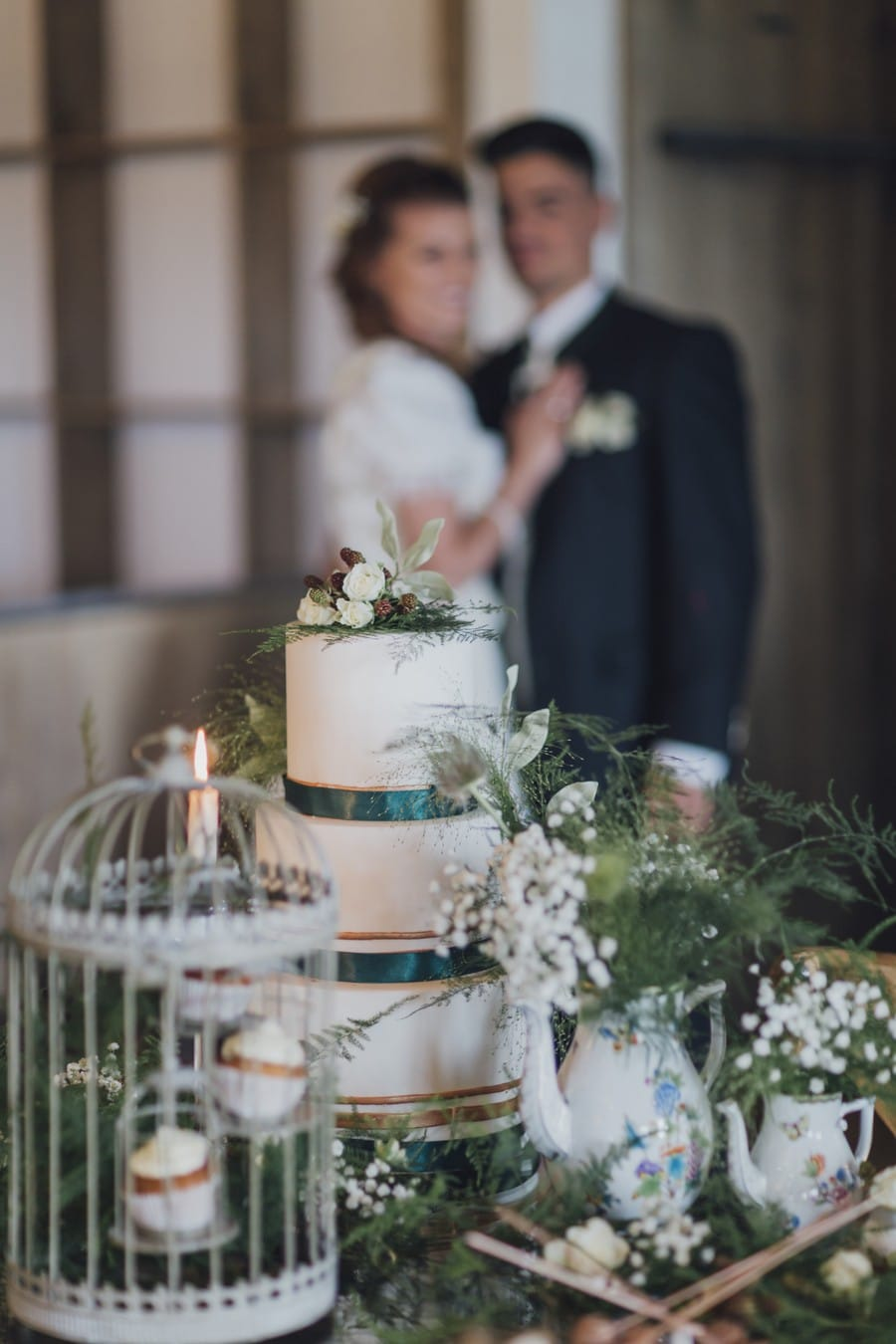 Ideen für eine Waldhochzeit mit viel Natur, Holz und Moos: Die klassische Hochzeitstorte mit dunkelgrünen Satinbändern