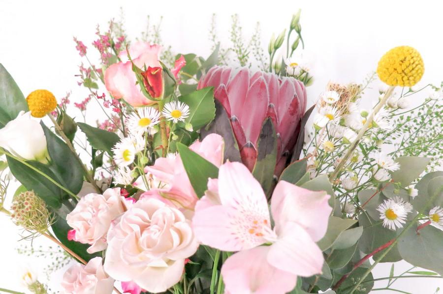 Blumenstrauß für den Trautisch mit schwarzer Vase, Protea und einem wildem Mix in Rosa und Grün