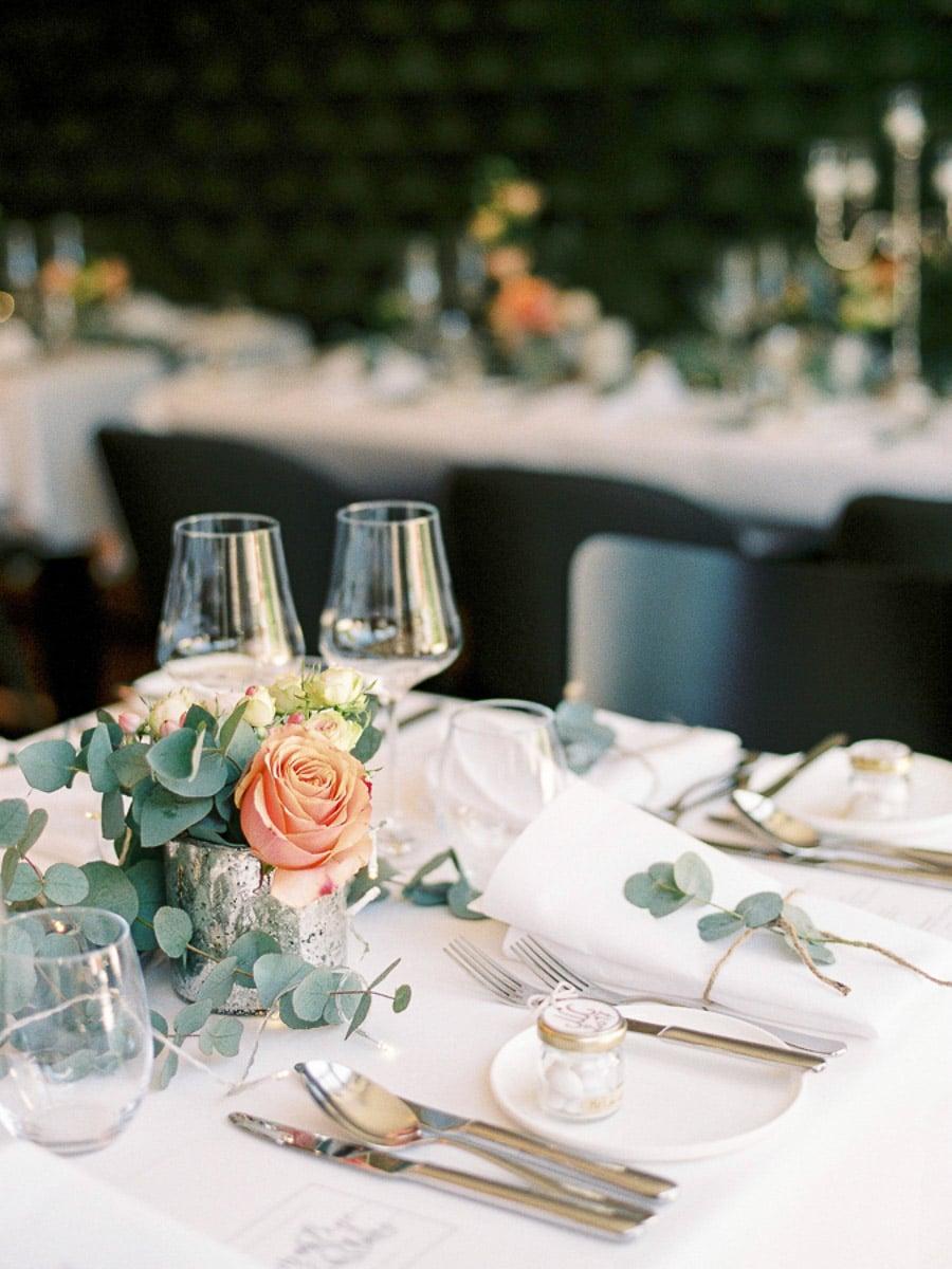 Klassische Vintage-Tischdeko bei einer Hochzeit mit Glas und rosa Rosen